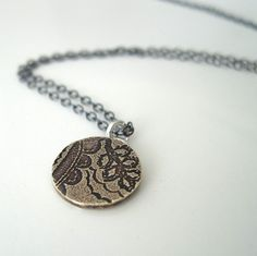 Tiny etched brass medallion necklace with a paisley pattern. $33.00, via Etsy.