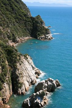 A stunning view over craggy cliffs and the azure ocean in the Abel Tasman National Park.