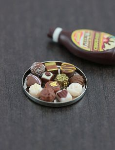 A round tray full of fancy various chocolate truffles, from dark bittersweets to caramel treats.  It would be a lovely add-on for a dollhouse pastry