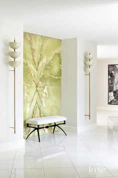 The dramatic entry focuses attention on a custom onyx wall. The owners are welcomed by vintage Stilnovo light fixtures from Van den Akker Antiques in New York flanking the onyx feature, and an Alexandre Logé bench from Donzella, also in New York. White Thassos marble flooring runs underfoot.
