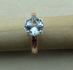 Natural cushion cut aquamarine set in 18k white gold setting with a hand milgrain allround 14k rose gold band. We designed and handmade this ring. The center is a 7 mm cushion cut aquamarine 1.43 cts. We can make it any size from 5-7 and you still be able to return it within the listed time frame. Sizing outside of that range requires a resize fee if for any reason the ring is retuned. Ring sizing may add additional handling time.  We love this ring because it represents the way jewelry…