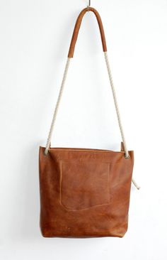 Leather Hobo with sturdy cognac colored leather and zip closure on top. Rope handles round up the raw look.