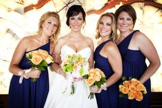 navy bridesmaid dresses with peach colored rose bouquet