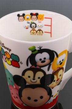 """Disney """"Tsum Tsum"""" Mug. The rounded """"Tsum Tsum"""" Disney characters suffer for the impossible cuteness that only Japan can do. The images are from toys that stack neatly upon one another, thus the delightful pile of faces on the mug. Interior """"Tsum Tsum"""" levels measure the fullness of your brew. Ceramic mug stands 4 inches and flares to 3 1/2 inches at the brim."""