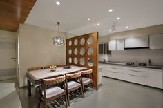 View of kitchen and dining space diving through a wooden partition having round cut outs with horizontal and vertical rods .Classy dining table with carved finishing and metal leg supports .Chairs also are very classy and attractive .Decent ceiling having lovely lighting element above ceiling .Kitchen with smash white surfaces .shaker cabinets and modern amenities .