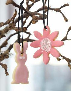 Als leckere Dekoration werden die Osterplätzchen mit Bastschleifen an knospende Zweige gehängt.