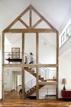 Stark white hallways and stairwells get a dose of warmth via natural wood stairs.