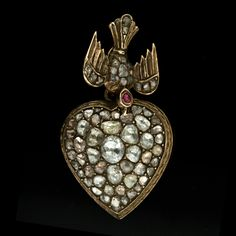 Late Georgian 14K yellow gold drop pendant featuring a diamond set bird motif with a ruby set head dangling a puffed heart encrusted with rose cut diamonds