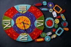 HODINY ŠPERKOVE Keramické nástenné hodiny glazúrované efektnými glazúrami. Veľkosť je 35 krát 31 cm, dĺžka aj s aplikáciami okolo 55 cm.