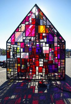 'kolonihavehus' by new york-based artist tom fruin in collaboration with coreact is an outdoor sculpture consisting of a thousand pieces of found plexiglass. located in the open riverfront plaza of the royal danish library in copenhagen, denmark, the installation largely resembles the form of a simple house clad in a vibrant and complex skin of plexiglass squares and steel framing, offering a visual and lighting effect close to a stained glass window.