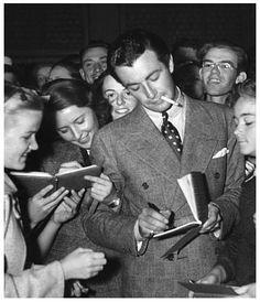 Barbara Stanwyck and husband Robert Taylor signing autographs