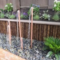 Use copper pipes with biased cut tops to create a pond-less water feature, possibly in a container rather than the yard