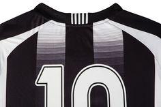 """Clássica, a camisa titular tem listras em preto e branco, gola retilínea em """"V"""" com friso na cor preta na parte da frente e detalhe de retilínea listrada na parte de trás"""