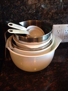 LOT OF MEASURING CUPS AND MIXING BOWLS IN BOTH METAL AND PLASTIC.