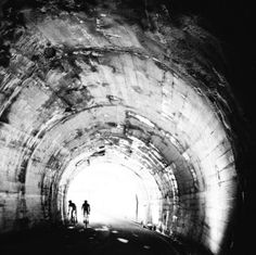 Two riders make their way through a mountain tunnel.