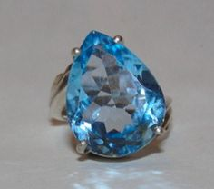 """The base of this ring is sterling silver, with a high polish.... In the very center is a massive pear shaped blue topaz measuring 20 mm's by 15 mm's... The blue topaz pear shaped is approximately 19.2 carats.. The band on this ring is very retro inspired with engraved etchings on each side of the center stone... This rings gives you a bold statement and the appearance of a fantastic white gold ring without the price tag... Marked, """"925"""" for sterling silver and """"AJ"""" for Alberto Juan... Upon…"""