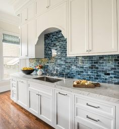 White and blue kitchen features white shaker cabinets paired with white marble countertops and a blue brick tile backsplash.