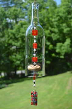 This wind chime is made from a clear wine bottle that I have cut myself. The edges have been sanded and it hangs from gold chain and rings. It has a wooden knocker and red, black, white and gold beads. Wind chime measures 25 long including chain and ring for hanging.