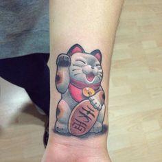 Neotraditional style Maneki-Neko tattoo on the left inner wrist.