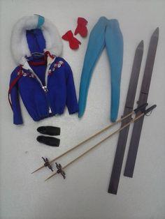"""SKI QUEEN: (mod.948, 1963 -´64) Blauw jack met rits en rood/witte versiering en capouchon met witte """"bont""""rand, licht blauwe ski-broek, rode wanten, zwarte ski schoenen, ski´s, ski-stokken en blauwe  zonnebril.Goede staat. SHEATH SENSATION: (mod.986, 1961 -´64) Rood jurkje met 4 goudkleurige knoopjes op het lijfje, stro-hoed met rood lint en open witte schoentjes(""""Japan"""") Goede staat. STORMY WEATHER/ RAINCOAT: (mod. 949, 1963) Gele regenjas met ceintuur, geel hoedje, witte laarsjes en…"""