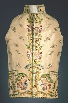 Waistcoat, France, 1785–90. Embroidered in coloured silk floss and chenille on an ivory silk taffeta ground. Overall small floral sprig, with a border of iris and other flowers down center front and across bottom. On the larger flowers at the bottom caterpillars in various shades of chenille are embroidered.