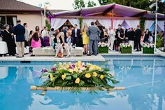 A huge arrangement of palm leaves and flowers floats in the pool on a bamboo boat | Luna Gardens Events