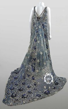 SOUPLETS Workshop (attributed to), circa 1910-1915 THEATRE COSTUME tulle embroidered with sequins and silver beads and blue with floral decoration, double straps, bra effect tassels emphasizing the chest, detachable long drags on the back (discoloration tulle , small gaps and snags)