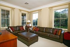 Living room or TV room this is a lovely room with light coloured walls, floor to ceiling curtains, large windows letting in the natural light  and patterned cornices. #livingrooms