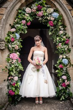 Bride standing under flower arch at church entrance