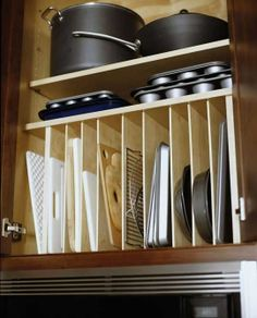 Cabinets. Built-in dividers for cookie sheets, pans, etc. Storage. Kitchen. Pots and pans. Kitchen idea. Home idea.