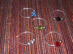 How to Make Wine Glass Charms. Wine glass charms, also called wine glass markers, are often used at parties because help keep track of which glass is whose. Charms, beads, or a combination of both are attached to a wire ring that fits. Liquor Bottle Crafts, Wine Glass Crafts, Wine Bottle Corks, Wine Craft, Beer Bottles, Cork Crafts, Shell Crafts, Diy Wine Glasses, Painted Wine Glasses
