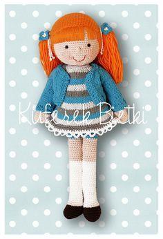 Nadine - lalka wykonana na szydełku. Lalka ubrana jest w sukienkę i sweterek wykonane na drutach. Włosy lalki upięte są w kucyki.