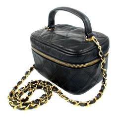 """Chanel - Vintage Vanity BagSUPER RARE version with crossbody shoulder strap Color: Black / Gold Material: Leather Details: - long crossbody shoulder strap with woven leather - gold tone hardware - zip around closure - interior slit pocket - serial number reads: 0826038 - item # AA1156 Condition: 4 out of 10 condition - gently used light has wear throughout ,light tarnishing at hardware creasing in leather shape Measurements: Length: 6"""" / 15.5 cm Height: 3"""" / 8 cm Dept..."""