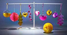 Boules de Noël en rose et jaune accrochées à un support