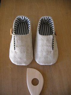 tecido exterior: meio linho. tecido interior: algodão. palmilha: algodão. enchimentos: flanela. fecho: cordão de algodão encerado. botões: madeira. dimensão: 12,0cm (aprox.10-12 meses).