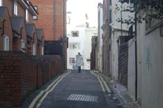 Photo taken down a alleyway capturing a moment with that laid walking towards the road with her bags in hand and show the differences of each side like on the right hand side looks all broke down were is on the left it has all right homes where people live.