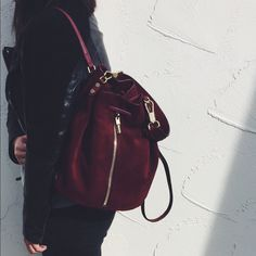 """Elizabeth & James Burgundy Suede Sling Backpack •Rich burgundy suede Cynnie bag from Elizabeth & James. Carry it by the optional top handle or sling the slim rolled straps over your shoulder.  •Drawstring closure, optional top handle, exterior zip pocket, interior zip, wall and smartphone pockets. Protective metal feet.  •11""""W x 12""""H x 5 ½""""D. 8 ½"""" strap drop.   •Suede with leather trim. Authenticity & care cards are included.  •New without tags/dust bag. Display bag so very minimal marks…"""