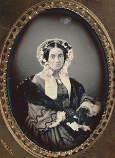 Arago, vers 1850, Portrait d/ Adelaide Streeter, Fonds Kodak-Pathé  Plaque dans un écrin en forme de livre entièrement recouvert de velours bleu nuit et doublé de satin blanc, sur cette doublure est épinglé une bande de papier avec une inscription. La plaque est encadrée sous verre, sous un passe-partout de métal doré à fenêtre ovale, entourée d'une frise de motifs guillochés. Constellé de taches brunes.