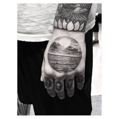 Sea landscape circle tattoo on the hand.