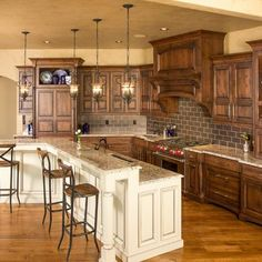 Rustic Two Toned Cabinets Design. I like the open storage above the cabinets with the blue plates! Nice variations in height with the stove hood going to the ceiling.