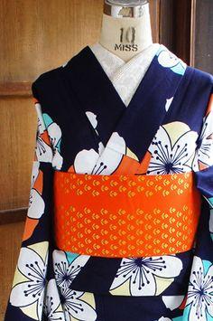 濃紺色の地にクリームイエローやオレンジ、空色などの愛らしいカラーに重なるように大きな桜のお花のモチーフが染め出された注染レトロ浴衣です。