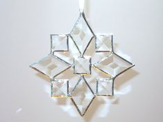 A shiny star snowflake stained glass suncatcher made of bevels. The suncatcher comes with a little wire hook adorned with glass beads. The seams are silver color. The dimensions are approximately 6 x 6 inches. Other snowflake sun catchers are sold individually in my shop http://etsy.me/18r1mZI OR you can BUY A SET OF 3 https://www.etsy.com/listing/110192380/ or a SET OF 6 http://etsy.me/1P48xYN and save! I photographed this stained glass suncatcher in different lighting to better display the…