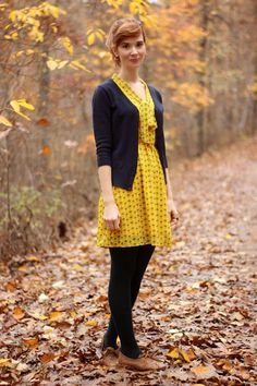 Cute fall outfit from Bleu Avenue: Yellow print dress, navy cardigan, tights and brown oxfords.