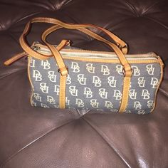 Dooney & Bourke Signature Bag Dooney & Bourke Signature Barrel Bag. It has minor stain inside bag and it has a key chain holder also. Dooney & Bourke Bags