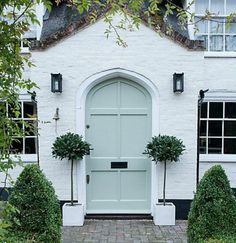 Magnificent white brick house exterior with soft minty green arched front door and pair of bay trees - John Lewis. White Brick Houses, White Exterior Houses, House Paint Exterior, Exterior Paint Colors, Exterior House Colors, White House Exteriors, Paint Colours, Exterior Design, Arched Front Door