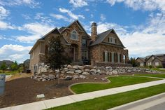 Gorgeous Utah home with beautiful rock, curbing, and grass.