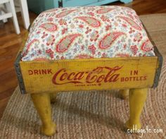 Here's a really creative way to create a useful piece of furniture with some awesome vintage flair. An old Coca Cola crate transformed into an ottoman for the living room.