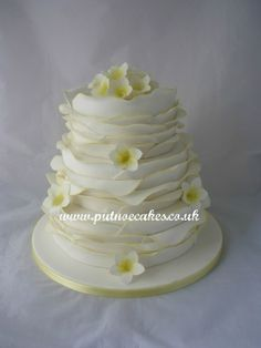 White and lemon wrap design wedding cake with frangipani flowers