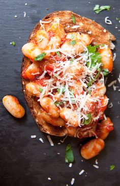 Beans and toast two ways: tomato baked beans with Parmesan and mashed white beans with ricotta and spinach.