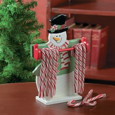 """Candy Cane Holder. Great for Christmas parties! Simply hang a row of candy canes for guests to enjoy. This snowman decoration also makes a welcome addition to your desk during the holiday season. Wooden with glitter accents on the scarf and white of the snowman's body. 10""""H x 7""""W."""